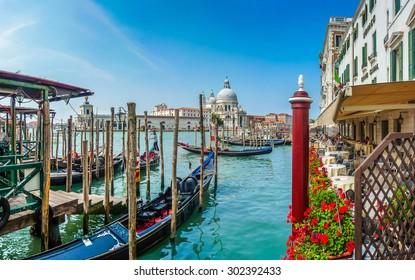 Beautiful view of traditional Gondolas on Canal Grande with historic Basilica di Santa Maria della Salute in the background on a sunny day in Venice, Italy