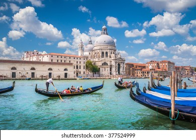 Beautiful view of traditional Gondolas on Canal Grande with historic Basilica di Santa Maria della Salute in the background on a sunny day with blue sky and clouds in Venice, Italy