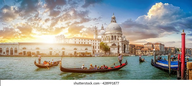 Beautiful view of traditional Gondolas on famous Canal Grande with historic Basilica di Santa Maria della Salute in the background in romantic golden evening light at sunset in Venice, Italy