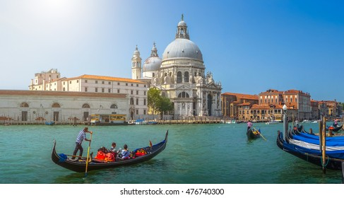 Beautiful view of traditional Gondolas on famous Canal Grande with historic Basilica di Santa Maria della Salute in the background on a sunny day with blue sky in summer, Venice, Italy
