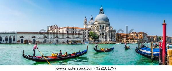 Schöne Aussicht auf die traditionellen Gondeln auf dem Canal Grande mit der historischen Basilica di Santa Maria della Salute im Hintergrund an einem sonnigen Tag in Venedig, Italien