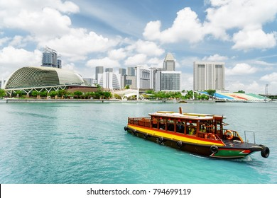 Beautiful view of traditional tourist boat sailing along Marina Bay with azure water in Singapore. Amazing modern buildings are visible on blue sky background. Scenic summer cityscape.
