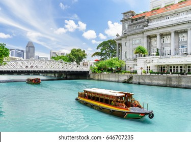 Beautiful view of traditional tourist boats sailing along the Singapore River with azure water in downtown of Singapore. Scenic summer cityscape. Singapore is a popular tourist destination of Asia.