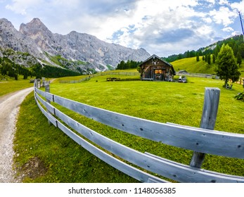 Beautiful view of traditional wooden mountain chalets on scenic Meadow in Italian Dolomites Mountain