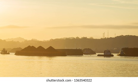 beautiful view of traffic of tugboats pulling barge of coal at Mahakam River, Samarinda, Indonesia at dawn. Mining and cargo industry background