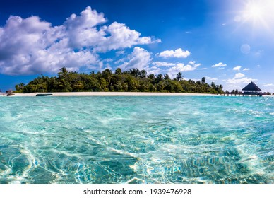 Beautiful view to a tropical island in the Maldives with turquoise sea, fine sand and coconut palm trees, Indian Ocean