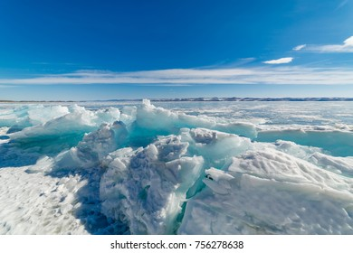 A beautiful view of the turquoise ice of a frozen lake against the background of snow-capped mountains and a blue sky with white clouds, a bright sunny winter day.