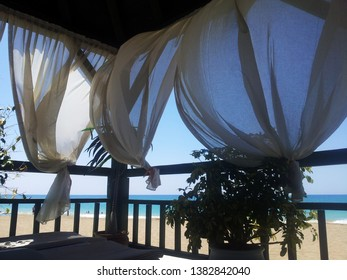 Beautiful view of the turquoise sea from the terrace with white curtains flying in the wind.