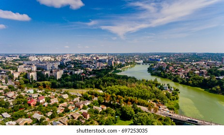 Beautiful view of a typical Ukrainian city surrounded by a green forest and a blue sky with white clouds. Aerial view.