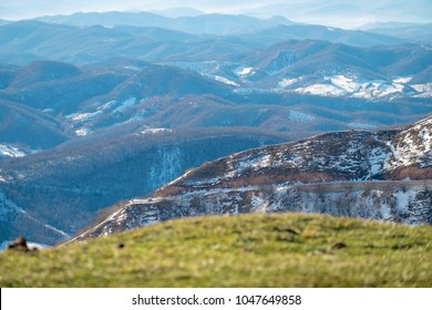 Beautiful view of umbria valley in Italy on a snowy winter morning with fog covering the mountains under a blue sky
