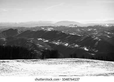 Beautiful view of umbria valley in italy on a snowy winter morning with fog covering the mountains in Black and White