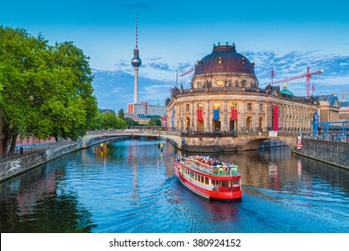Beautiful view of UNESCO World Heritage Site Museumsinsel (Museum Island) with excursion boat on Spree river and famous TV tower in the background in beautiful evening light at sunset, Berlin, Germany