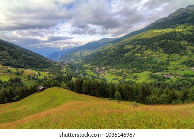 Beautiful view of the Val d'Anniviers valley in Switzerland with the villages saint-luc, saint-jean and vissoie in summer with green fields