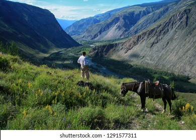 Beautiful view of the Valley of Chulyshman river and a man with a horse on Altai in Russia