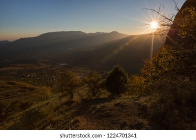 Beautiful view of the valley in the sun rays in the mountains Demerdzhi and yellow trees in the autumn Crimea