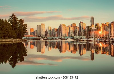 Beautiful view of Vancouver skyline with famous Stanley Park in scenic golden evening light at sunset with retro vintage Instagram style pastel toned filter effect in summer, British Columbia, Canada