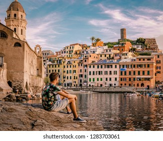 Beautiful view of Vernazza .Is one of five famous colorful villages of Cinque Terre National Park in Italy, young men sitting on a rock at the harbour of Vernazza