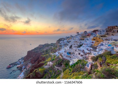 Beautiful view of the village Oia on Santorini island at dusk with colorful twilight and white houses, windmill on the cliff, Greece.