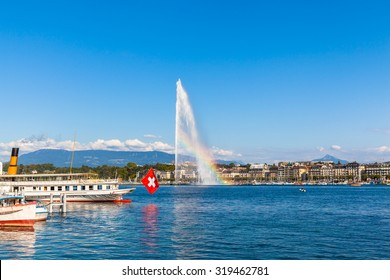 Beautiful view of the water jet fountain with rainbow in the lake of Geneva and the cityscape of Geneva at sunset, Switzerland