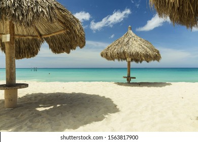 Beautiful view of white sand beach with sun umbrellas and sunbeds. Eagle beach. Aruba island.