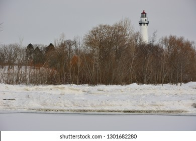 A beautiful view of the Wind Point Lighthouse off the shore of Lake Michigan on a bitter cold February day with icebergs along the shore from the frozen waters.
