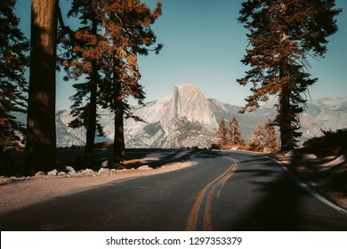Beautiful view of winding Glacier Point Road with famous Half Dome summit in golden evening light at sunset in fall, Yosemite National Park, California, USA