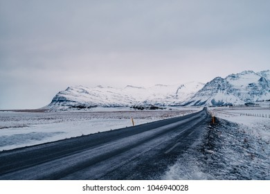 Beautiful View and winter landscape of Iceland's golden circle road during the sunset with the snow-capped mountain as a background and the road asphalt as a foreground.