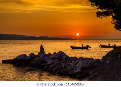 beautiful view with the woman sitting on the stones and watching the sunset, Croatia