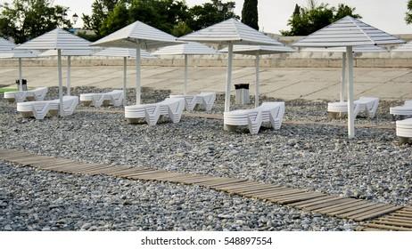 Beautiful view of wooden sunbeds, beach