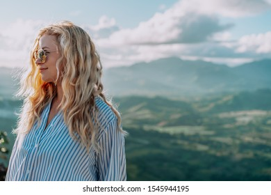 Beautiful view of young woman in sunglasses smiling on the top of the mountain on the dawn. Great landscape. Concept travel, dream