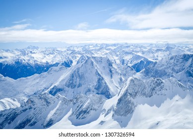 Beautiful view of Zugspitze mountain. The highest place in Bavaria, Garmisch-Partenkirchen, Germany. Snowy peaks of the Alpine Mountains. View of the observation deck at the top of Zugspitze.