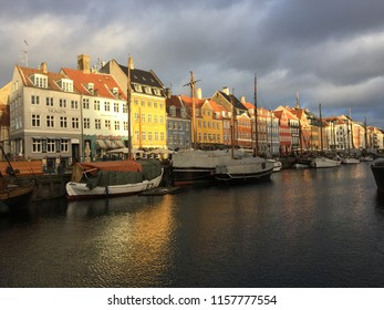 Beautiful views of the canal, the shore with houses, yachts, sailboats and barges. Sunset with cloudy weather. January 30, 2018. Nyhavn, Copenhagen, Denmark.