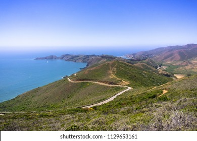 Beautiful views of the green hills of Marin Headlands crossed by a winding road; the Pacific Ocean coastline in the background; north San Francisco bay area, California