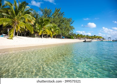 Beautiful views of the resort on the island of Mauritius. Transparent ocean, white sand, palm trees on a background of clouds