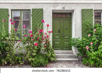 Beautiful views of Visby, main city on Gotland, island in Baltic Sea in Sweden.Best-preserved historical medieval city in Scandinavia. Front view of white stone house with green wooden door, shutters.