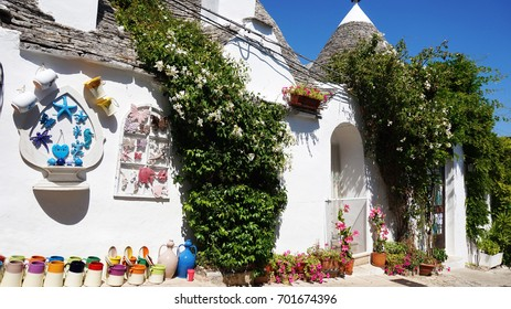 Beautiful village of Alberobello with trulli houses among green plants and flowers, main touristic district, Apulia region, Southern Italy