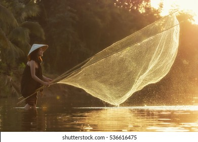 A beautiful Village women fishing sunrise at the nature river, countryside and Folkways concept