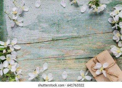 Beautiful vintage background from old blue boards, white spring flowers and gift box