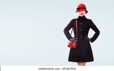 Beautiful vintage European style winter fashion look woman. Isolated on light blue background. Red hat,shoulder bag, and black wool coat.