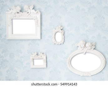 Beautiful vintage frames with Cupids on tender blue damask background. Wall with photo gallery