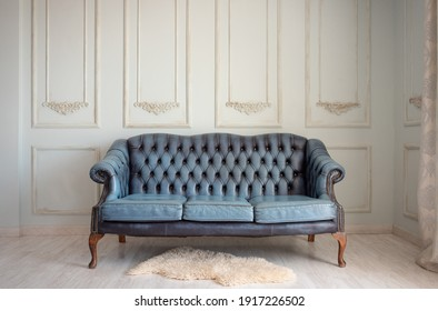 Beautiful vintage sofa in blue on a vintage wall background.