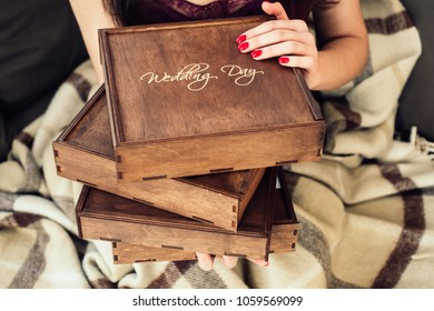 Beautiful vintage wooden box for wedding photobook in woman's hands