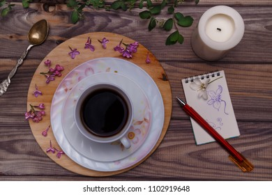 Beautiful violet lilac flowers with white cup with coffee or tea, on a wooden background