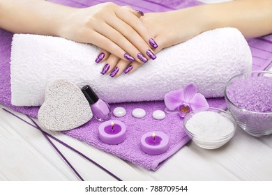 beautiful violet manicure with decor, orchid, towel and candle on the white wooden table. spa