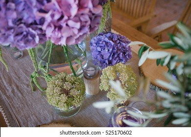 Beautiful violet peonies and other flowers in simple glass vases