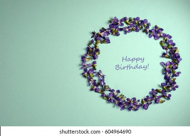 Beautiful violets in circle form on light blue background