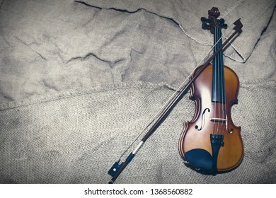beautiful violin rests on an old piece of material.