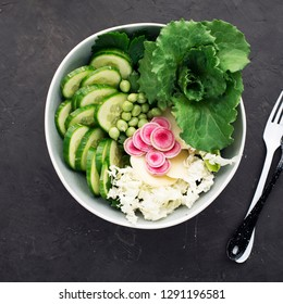 Beautiful vitamin healthy vegetable salad. Cucumbers, cabbage, daikon, lettuce, young peas in the same bowl. Top view