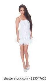 Beautiful vivacious woman with a lovely smile posing in a stylish short white cocktail dress trimmed with feathers and wearing stilettos