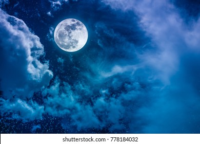 Beautiful vivid cloudscape with many stars. Night sky with bright full moon and cloudy, serenity blue nature background. Outdoor at nighttime with moonlight.